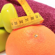 Dumbbells and towel for using in fitness, fresh fruit with tape measure — Stock Photo #61714571