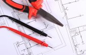 Cables of multimeter and work tool on construction drawing — Stock Photo
