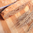 Hand of woman slicing fresh bread, ears of wheat — Stock Photo #64846243