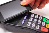 Hand of woman paying with NFC technology on mobile phone — Stock Photo