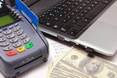 Payment terminal with credit card, money, laptop and financial calculations — Stock Photo