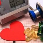 Stethoscope, heart shape, blood pressure monitor on electrocardiogram — Stock Photo #66789431