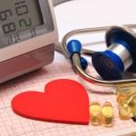 Heart shape on electrocardiogram, blood pressure monitor, stethoscope — Stock Photo #66789455