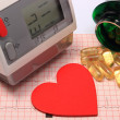 Heart shape, blood pressure monitor and tablets on electrocardiogram — Stock Photo #67361465