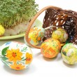 Easter eggs in overturned wicker basket and green cuckooflower — Stock Photo #67372801