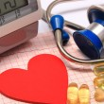 Heart shape on electrocardiogram, blood pressure monitor, stethoscope — Stock Photo #68616375