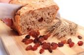 Slicing fresh bread, ears of wheat and raisins — Fotografia Stock