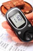 Glucometer in hand and portion of chocolate on medical form — Stock Photo
