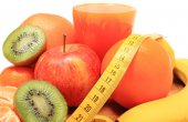 Fresh fruits, tape measure and glass of juice — Стоковое фото