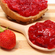 Fresh fruits and strawberry jam on wooden cutting board — Stock Photo #70028381