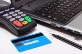 Payment terminal with credit card, laptop and financial calculations — Stock Photo