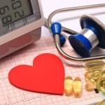 Heart shape on electrocardiogram, blood pressure monitor, stethoscope — Stock Photo #71213193