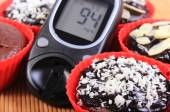Glucose meter and chocolate muffins in red cups — Stock Photo