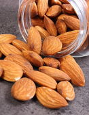 Almonds spilling out of glass jar on concrete structure — Stock Photo