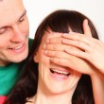 Hombre que cubre los ojos de una mujer por sorpresa — Foto de Stock   #75866755