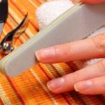 Woman polishing fingernails with nail file — Stock Photo #77691134