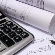 Rolls of electrical diagrams, calculator and mathematical calculations — Stock Photo #77691148