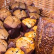 Freshly baked muffins and breads in basket — Stock Photo #79205004