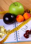 Fruits, tablets supplements and centimeter with notebook, slimming and healthy food — Zdjęcie stockowe