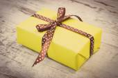 Vintage photo, Yellow gift for Christmas or other celebration on wooden plank — Stockfoto