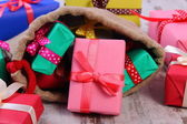 Wrapped gifts in jute bag for Christmas or other celebration — Stock Photo