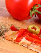 Slice of vegetarian pizza, tomatoes and seasoning on wooden surface — Stock Photo