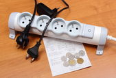 Electrical cords disconnected from power strip, electricity bill — Stock Photo