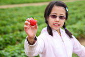 Girl Holding Up a Strawberry — Stock Photo