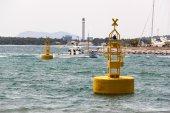 Yellow buoys and sailor boat — Stock Photo