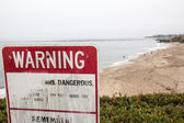 Red attention sign on beach with people — Stock Photo