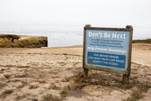 Blue attention sign on beach — Stock Photo