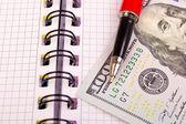 Pen en dollars zijn op de notebook — Stockfoto