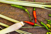 Chili and lemon grass on an old wooden background. — Stock Photo