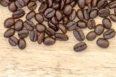 Coffee beans on wooden floor — Stock Photo