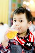 Young boy look at camera and drink orange juice — Stock Photo