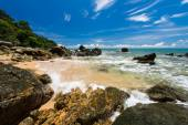 Sea waves lash line impact rock on the beach under blue sky — Stock Photo