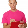 Man in pink shirt writes document — Stock Photo #63562173