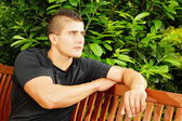 Muscular man sits on the bench — Stock Photo