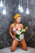 Model in a green knitted bikini stay with bouquet of flowers — Stock Photo