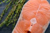 Raw salmon with thyme on a wooden board. close-up — Stock fotografie