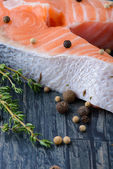 Raw salmon with thyme and pepper on a wooden board. close-up — Stock fotografie