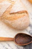 A loaf of bread with a spoon on the table — Stock Photo