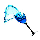 Glass with blue liquid with a splash — Stock Photo