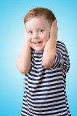 Little boy with closed ears on a blue background — Foto de Stock
