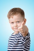 Little boy with his thumb on a blue background — Stock Photo