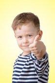 Маленький мальчик с его пальца на желтом фоне — Стоковое фото