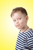 Little boy in a striped vest on a yellow background — Stock Photo