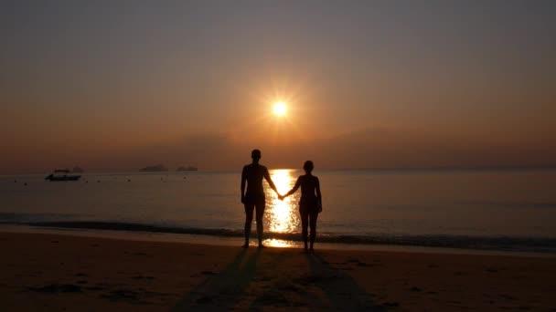 Romántica pareja cogidos de la mano y disfrutando de playa puesta del sol. — Vídeo de stock