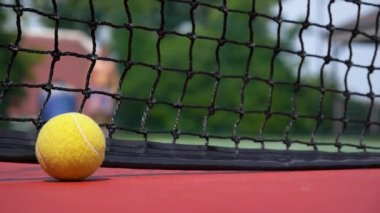 Tennis Ball on the Court Close up with the Net Beyond — Stock Video
