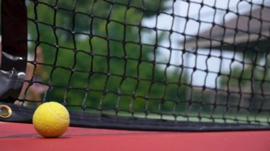 Tennis Ball on the Court with the Net in the Background — Stock Video